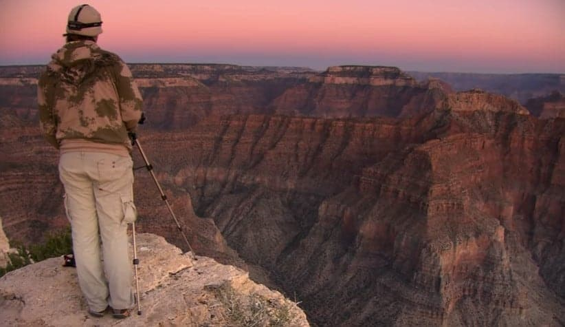 a man standing in front of grand canyon in arizona