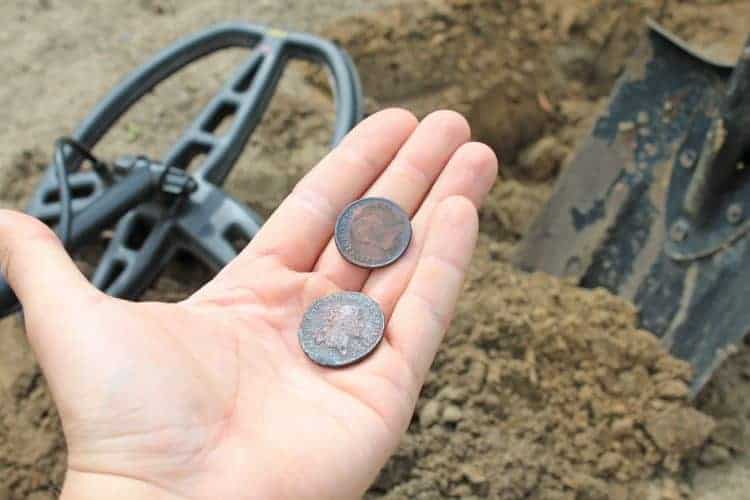 man finds a coin while metal detecting