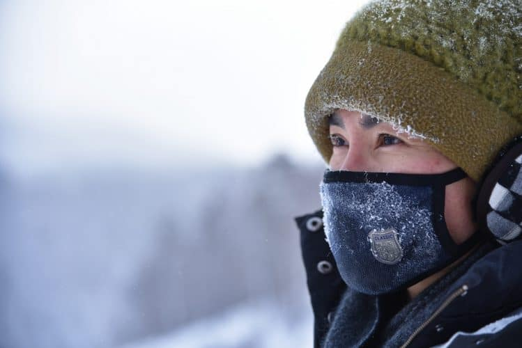 a woman with a winter hat and a mask