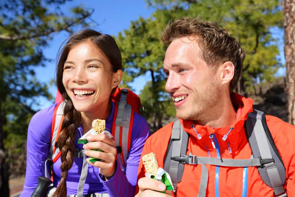 a couple eating energy bars while hiking
