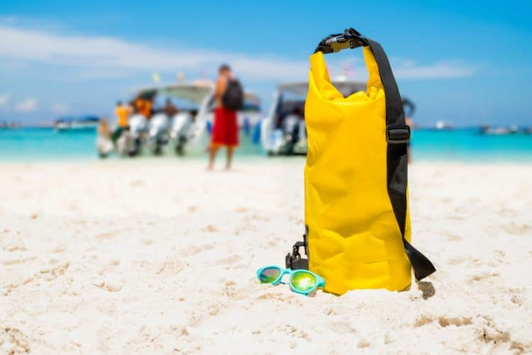 Yellow waterproof shoulder bag with sunglasses on beach sand at