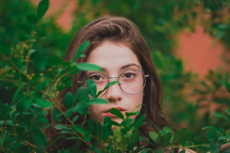 a girl wearing spectacles in nature