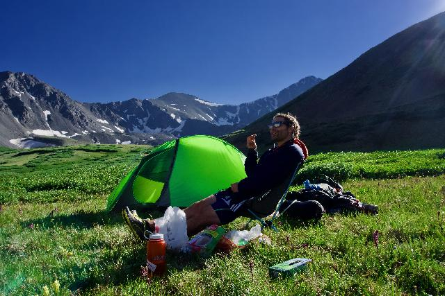 a hiker chills near his tent