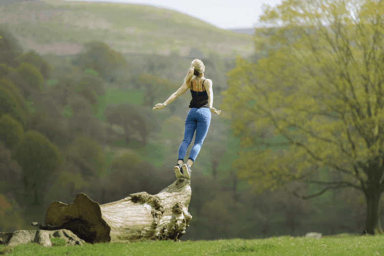 woman jumping off a tree