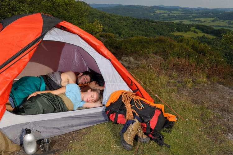 a couple sleeping in a tent