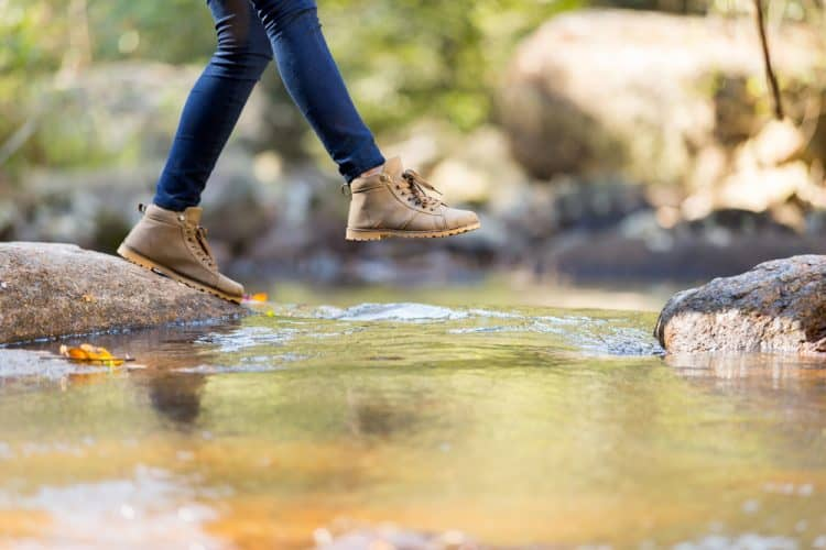 a girl crossing a stream with jeans