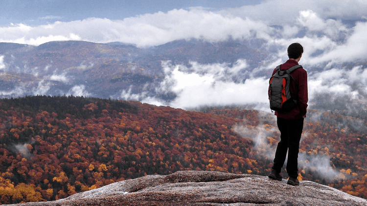 fall hiking and a man standing on a rock