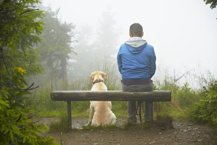 man sitting on a bench with his dog
