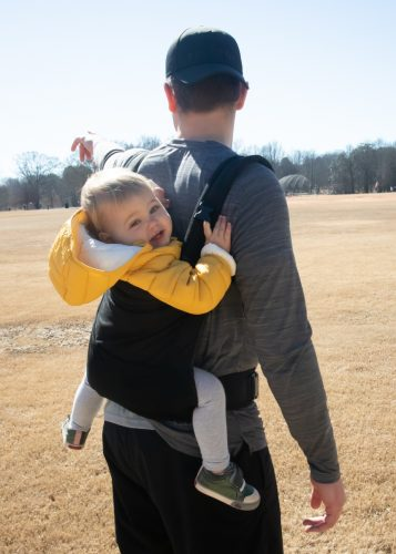 a hiking dad with his baby in the co carrier