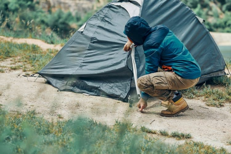 a man putting tent pegs