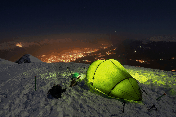 a warm tent up on a hill at night
