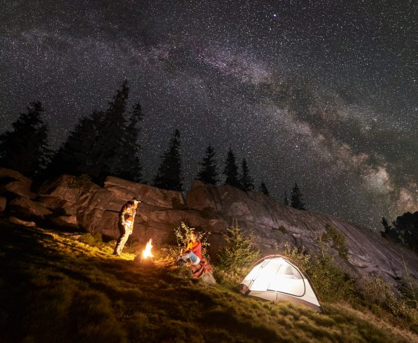 Night summer camping in the mountains under night starry sky