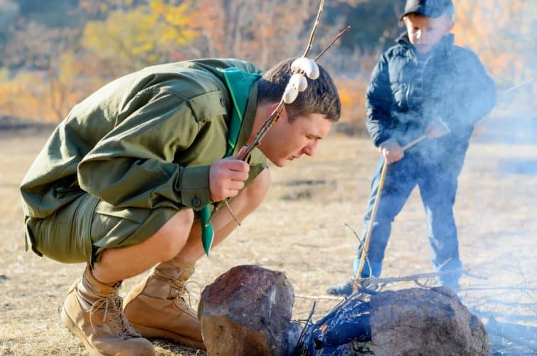 a man blowing on a campfire