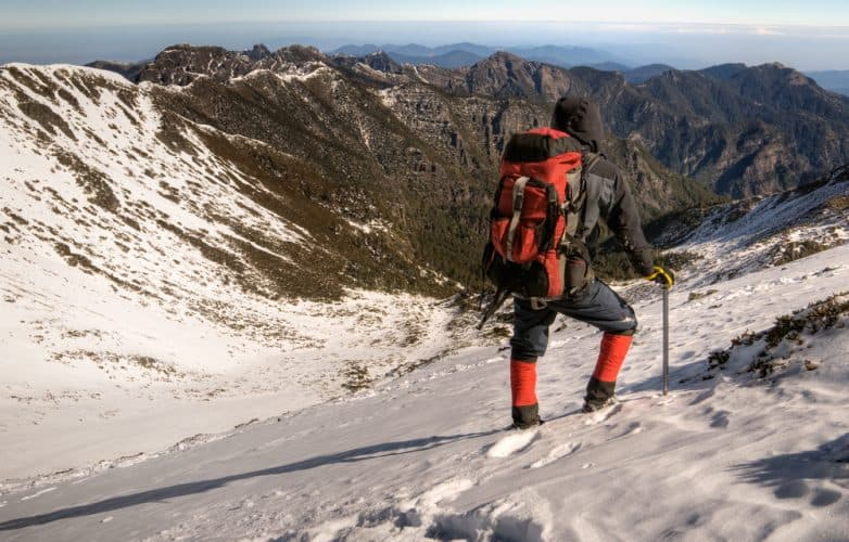 man hiking on a snowy mountain hill