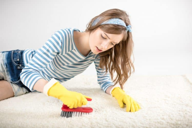 a girl cleaning a tent carpet