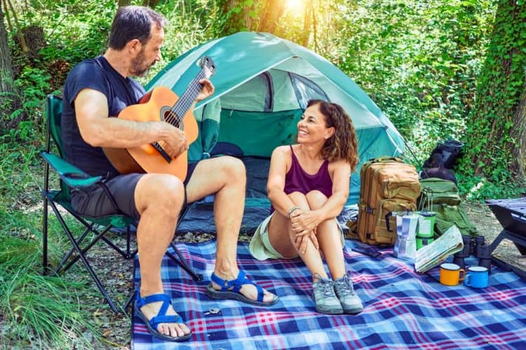 a couple camping sitting on a tent carpet