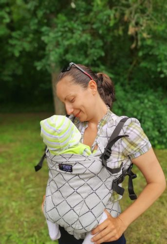 a baby in an ergonomic child carrier