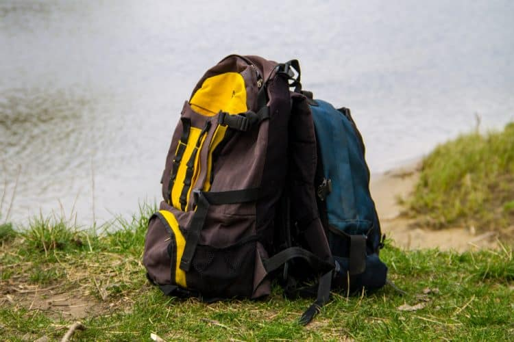 a backpacking backpack next to a tree