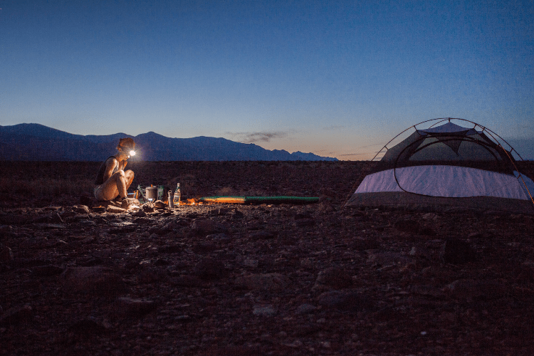 woman camping in the dark